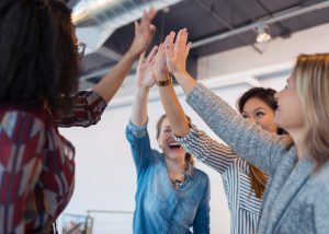 Businesswomen high fiving in conference room