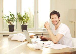 Confident Smiling Man Working At Desk
